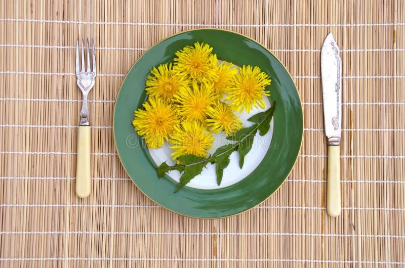 Nourriture végétarienne naturelle de printemps sain de fleurs et de feuilles de pissenlit photo libre de droits