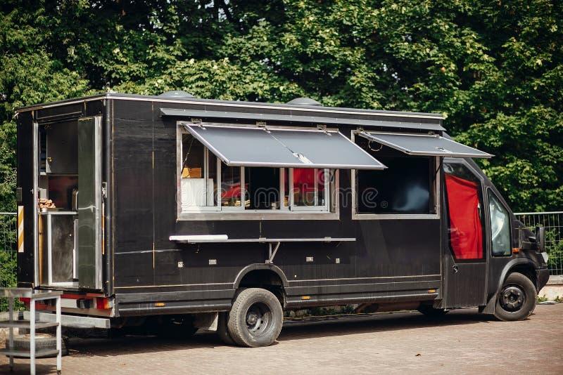 Nourriture van truck Camion mobile noir élégant de nourriture avec les hamburgers et la nourriture asiatique au festival de nourr photos stock