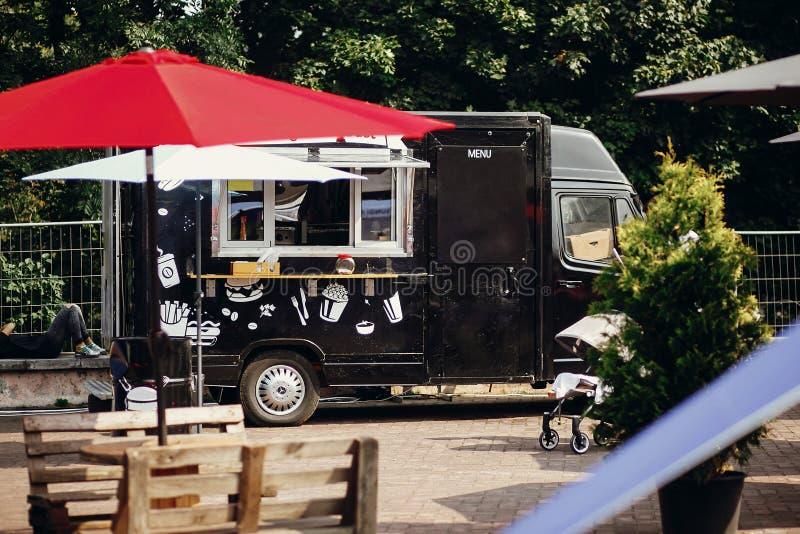 Nourriture van truck Camion mobile noir élégant de nourriture avec les hamburgers et la nourriture asiatique au festival de nourr images libres de droits