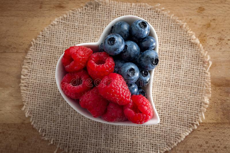 Nourritures saines et bon concept d'habitudes alimentaires avec un bol blanc en forme de coeur de myrtilles et de framboises renv images stock