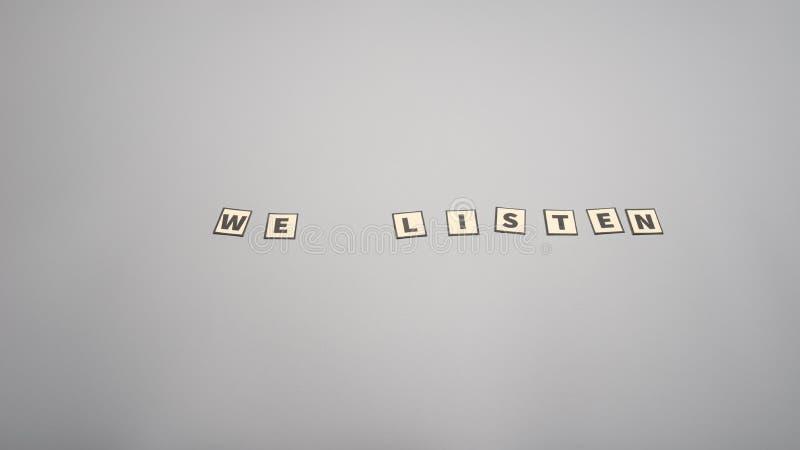 Nous écoutons signe assemblé avec les lettres coupées de papier photo stock