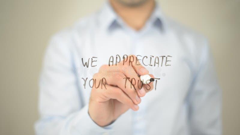 Nous apprécions votre confiance, écriture d'homme sur l'écran transparent photo libre de droits