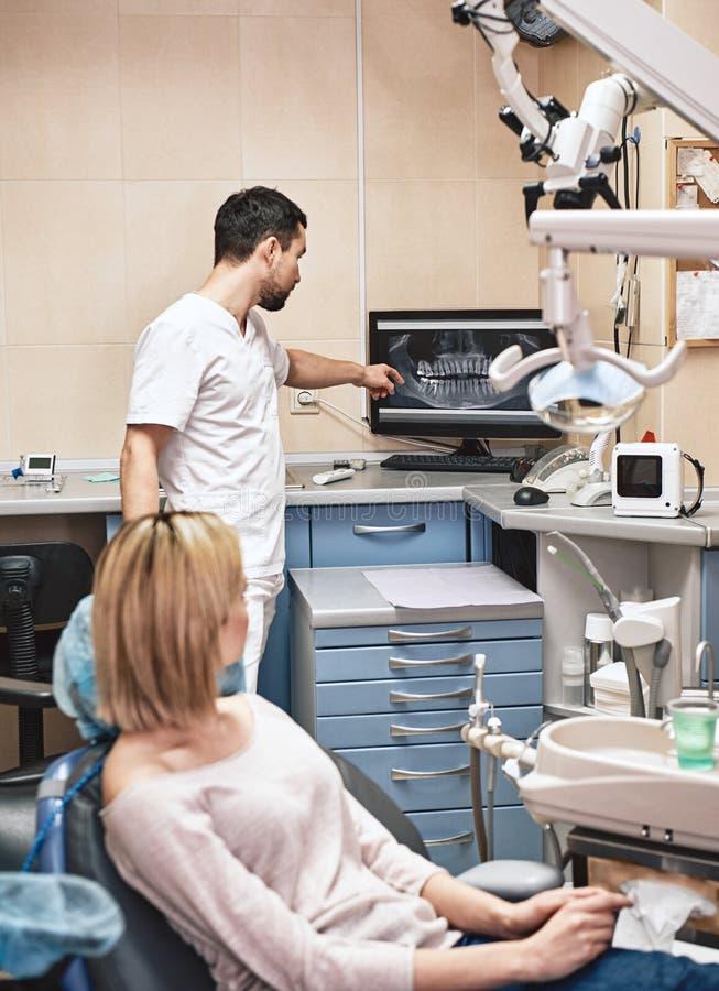 Nous sommes les fabricants de sourire Le dentiste explique en d?tail le progr?s du traitement dentaire patient dans la clinique m photos libres de droits