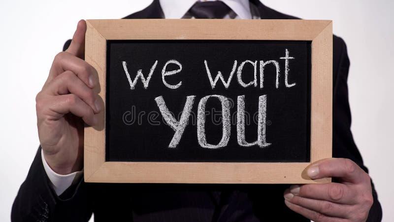 Nous voulons que vous exprimiez sur le tableau noir dans des mains d'homme d'affaires, offre d'emploi prometteuse image stock