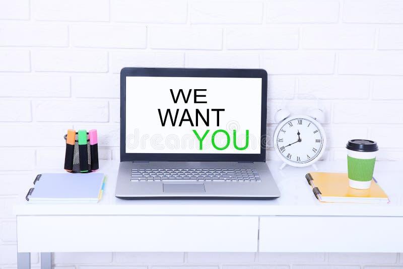 Nous vous voulons Mots sur le moniteur Lieu de travail avec l'ordinateur et la tasse de café L'espace élégant de copie Voir les m photo stock
