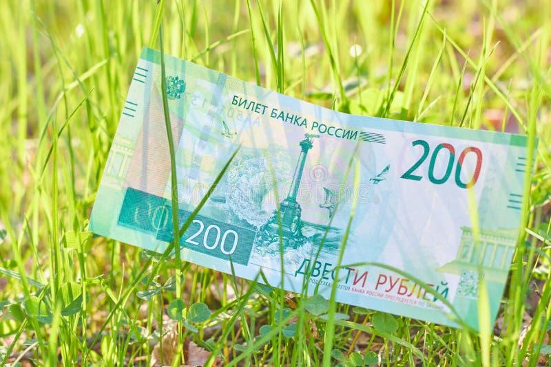 Nouveau billet de banque russe deux cents roubles dans l'herbe verte en temps clair Argent vert russe de papier d'argent liquide photo libre de droits