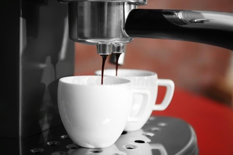 Nouveau fabricant de café versant l'expresso frais dans deux tasses, images stock