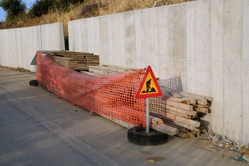 Nouveau mur en béton renforcé, avec le panneau d'avertissement de route photos stock