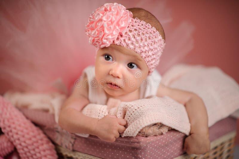 Nouveau-né dans un panier sur fond rose images stock