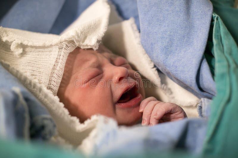 Nouveau-nés, les yeux se sont fermés, bébé pleurant dans la couverture verte dans l'hôpital photographie stock libre de droits