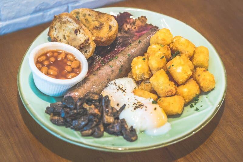Nouveau Ol' English Fry Up Garlic and herb beef saucisse, haricots cuits au four, bacon de boeuf, toast à l'ail, oeufs sous vide, photo stock