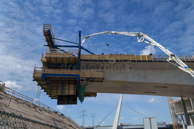 Nouveau pont en route étant construit La nouvelle partie accroche dans le ciel photo libre de droits