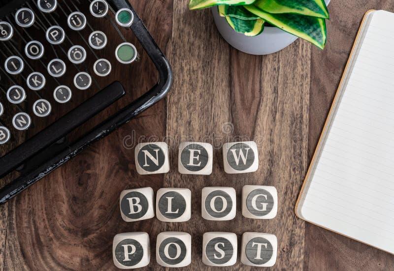 NOUVEAU POTEAU de BLOG de mots sur les blocs en bois sur la table avec le bloc-notes, l'usine mise en pot et la machine à écrire  images stock