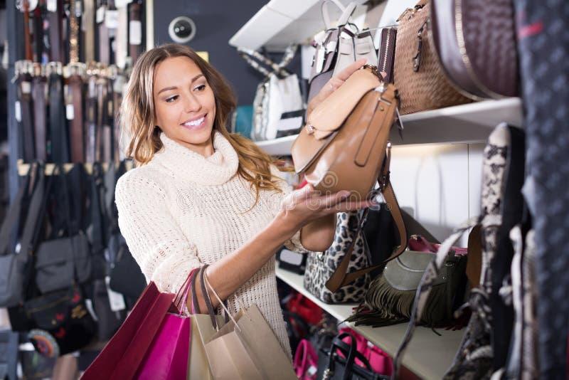 Nouveau sac à main de jeunes achats femelles enthousiastes dans la boutique photos stock