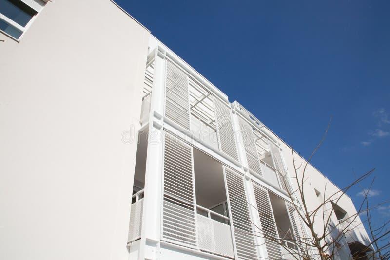 Nouveaux bloc multifamilial avec des balcons et lumineux sur le ciel bleu image stock