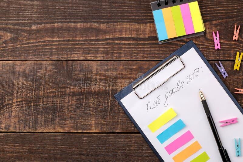 Nouveaux buts pour 2019 Texte sur le papier avec des autocollants de couleur sur un fond en bois brun photographie stock libre de droits