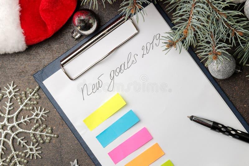 Nouveaux buts 2019 Texte sur un morceau de papier avec un stylo et décoration de nouvelle année sur un fond foncé image stock