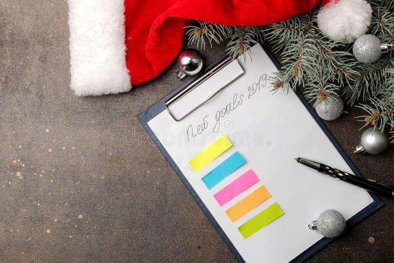Nouveaux buts 2019 Texte sur un morceau de papier avec un stylo et décoration de nouvelle année sur un fond foncé photo stock