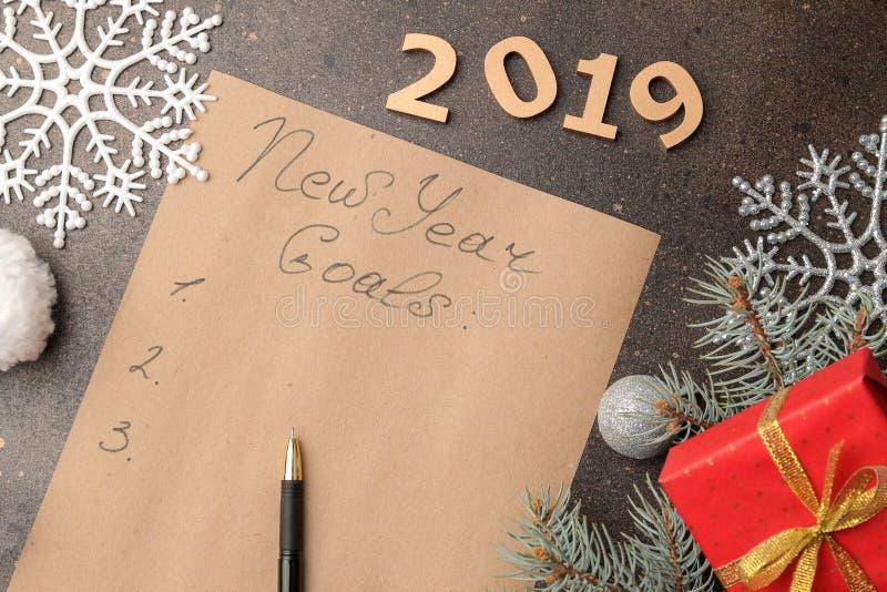 Nouveaux buts 2019 Texte sur un morceau de papier avec un stylo et décoration de nouvelle année sur un fond foncé image libre de droits