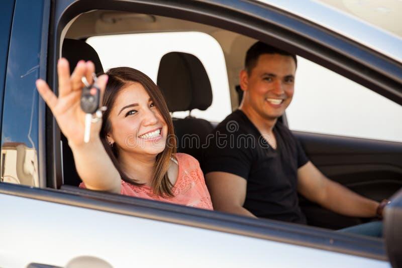 Nouveaux mariés avec une nouvelle voiture image stock
