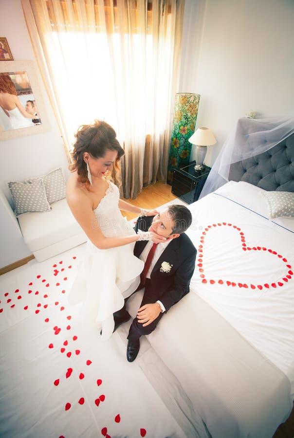 Nouveaux mariés dans la chambre à coucher avec le coeur images libres de droits