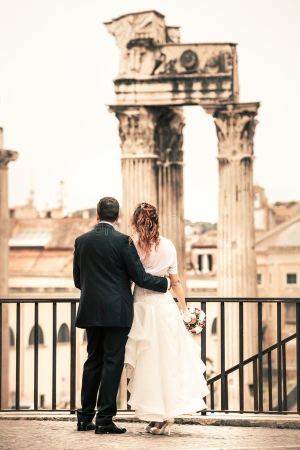 Nouveaux mariés dans la ville antique Ménages mariés heureux Beaux vieux hublots à Rome (Italie) image stock