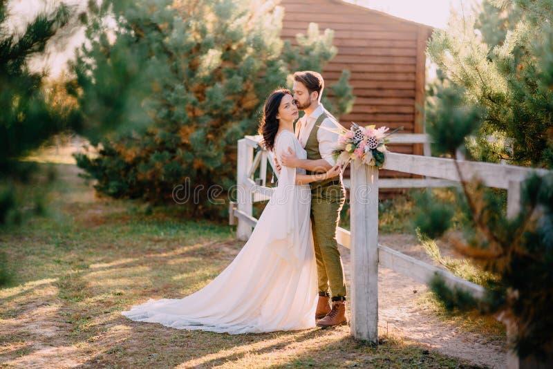 Nouveaux mariés dans le style de cowboy se tenant et étreignant sur le ranch photos stock