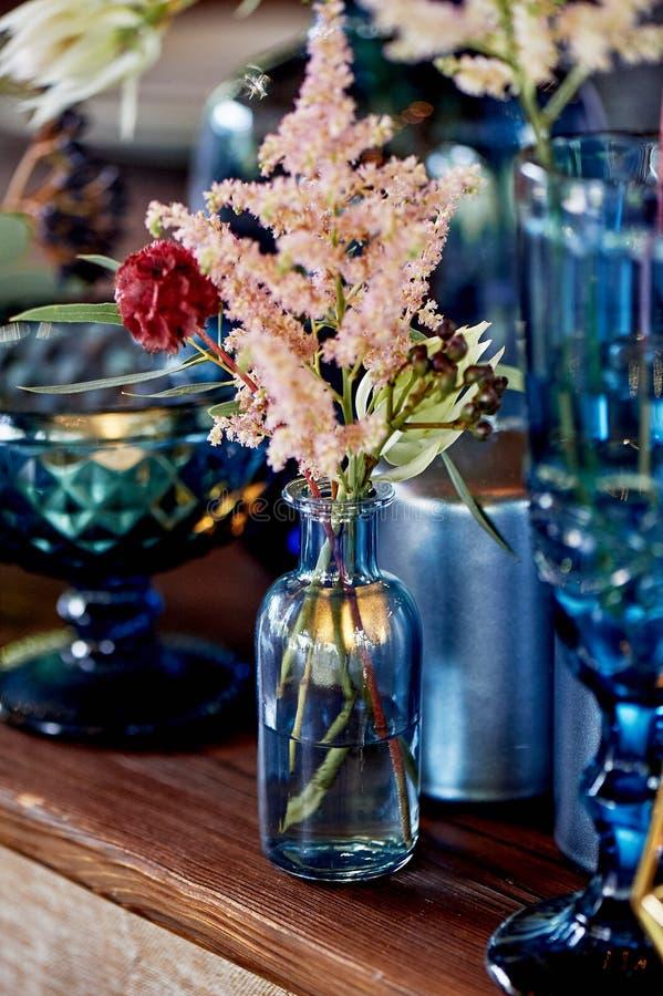 Nouveaux mariés de table de décoration, plats bleus, bouteilles de fleurs et bougies ?pouser floristry images stock