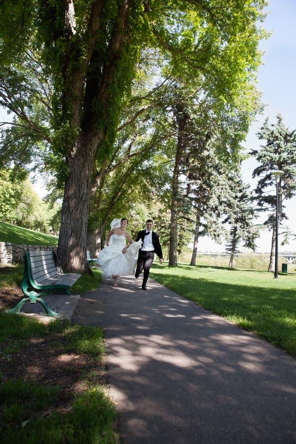 Nouveaux mariés exécutant le long du passage couvert photographie stock