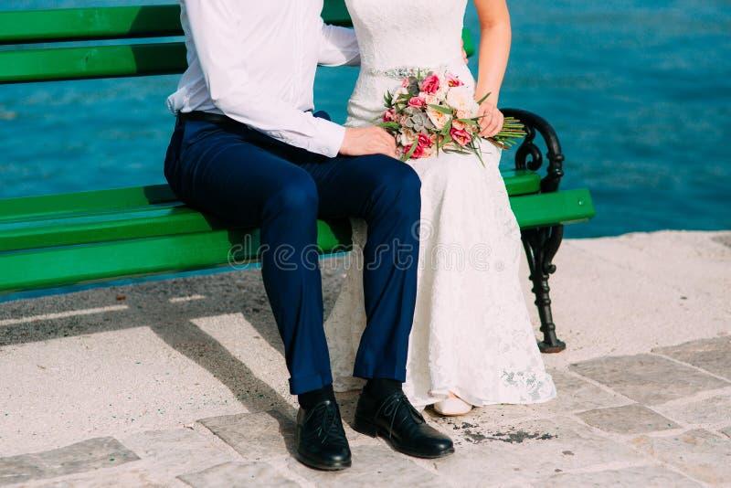 Nouveaux mariés sur le banc Jambes en gros plan photographie stock