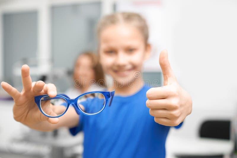 Nouveaux verres dans des mains d'enfant dans le magasin optique photos libres de droits