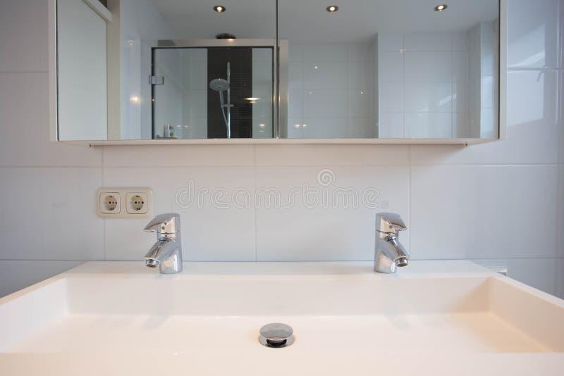 Nouvel évier de salle de bains avec deux robinets argentés photo libre de droits