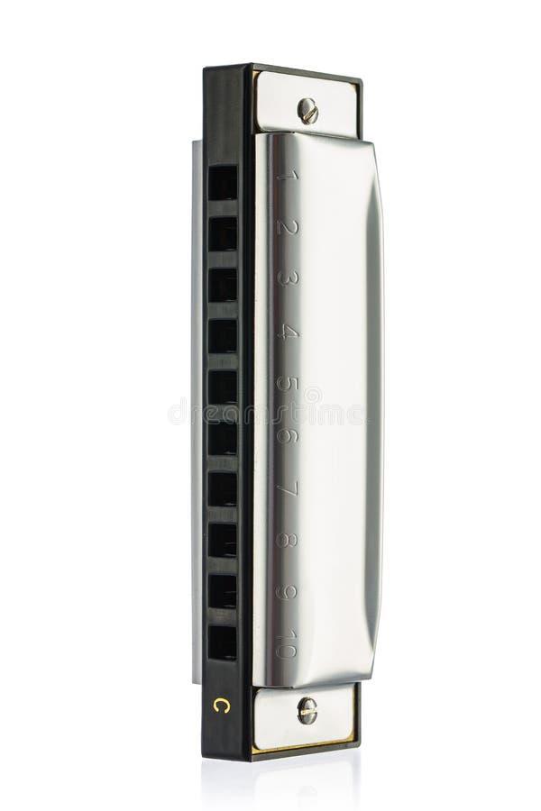 Nouvel harmonica classique de métal sur un fond blanc photographie stock