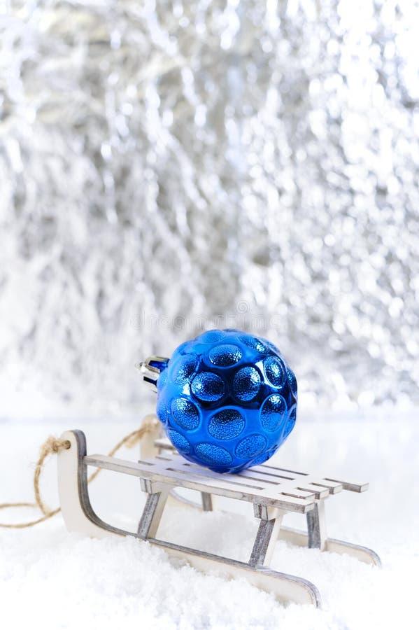 Nouvelle année, carte de voeux de Noël Petits traîneaux en bois décoratifs de jouet sur la neige avec une boule bleue lumineuse d photographie stock libre de droits