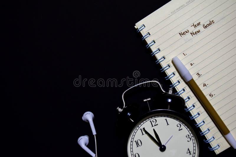 Nouvelle année - les nouveaux buts textotent sur le carnet, réveil, le stylo de couleur, écouteur sur le fond noir image stock