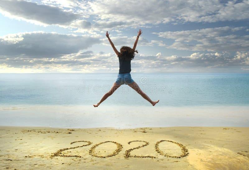 Nouvelle année 2020 sur le sable, fille heureuse avec des mains vers le haut de sauter sur la plage photographie stock