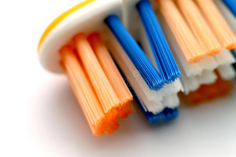 Nouvelle brosse à dents avec les poils jaunes, bleus et blancs sur le plast images stock