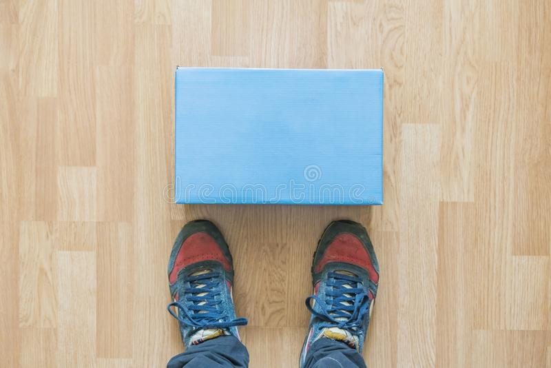 Nouvelle configuration delievered de colis devant des jambes à l'intérieur sur le plancher f photos stock