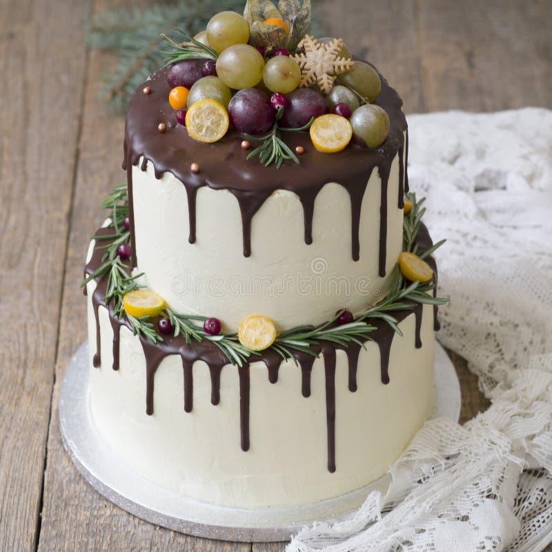 Nouvelle gâteau à deux niveaux blanc d'année ou de Noël, décoré du kumquat, des brins du romarin et des canneberges sur un en boi photographie stock