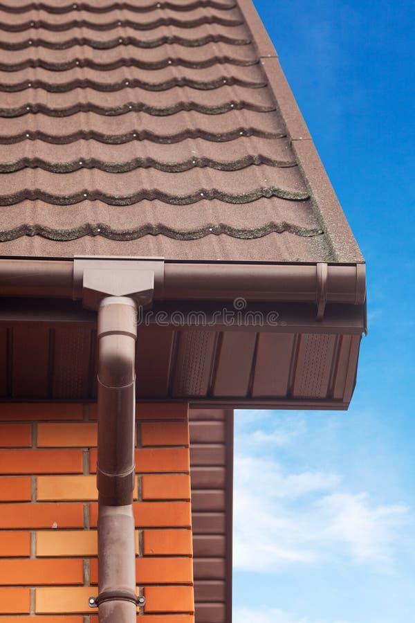 Nouvelle gouttière blanche de pluie sur un toit avec la canalisation, la tuile enduite en pierre en métal, les soffites en plasti images libres de droits