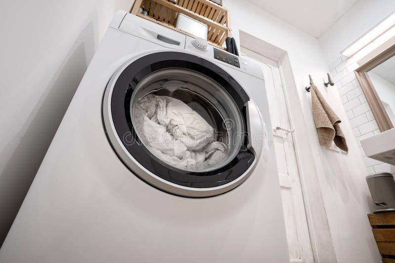Nouvelle machine à laver avec la literie à l'intérieur, à l'intérieur d'une salle de bains lumineuse avec des étagères photographie stock libre de droits