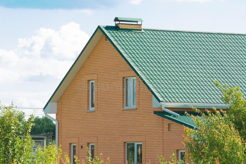 Nouvelle maison de brique avec la cheminée modulaire, la tuile de toit enduite en pierre en métal, les fenêtres en plastique et l image stock