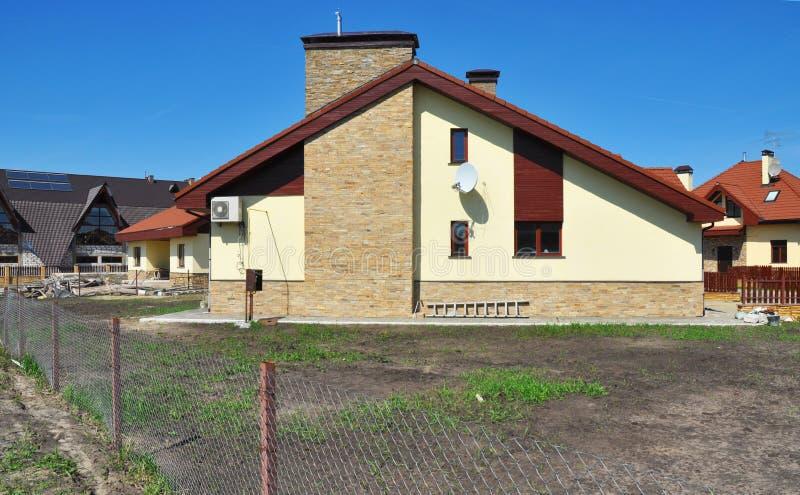 Nouvelle maison moderne de construction avec la cheminée anglaise de la pierre naturelle photo stock