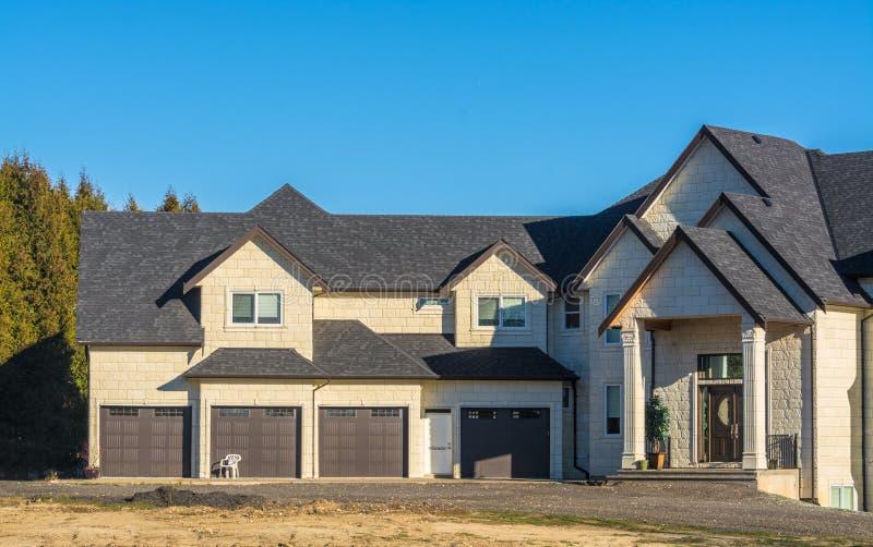 Nouvelle maison résidentielle géante avec le garage de quatre stalles photos stock