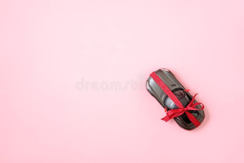 Nouvelle voiture moderne avec le ruban rouge d'arc comme pr?sent Cadeau de voiture de jouet sur le fond rose, composition ?tendue photo stock