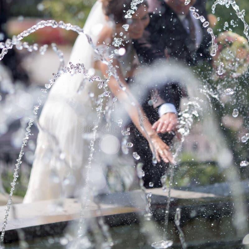 Nouvellement épousé derrière la fontaine photos libres de droits