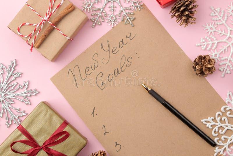 Nouvelles années de buts 2019 Texte sur un morceau de papier avec un décor de nouvelle année et un stylo sur un fond rose lumineu photos libres de droits