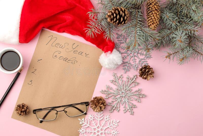 Nouvelles années de buts 2019 Texte sur un morceau de papier avec un décor de nouvelle année et un stylo sur un fond rose lumineu photographie stock