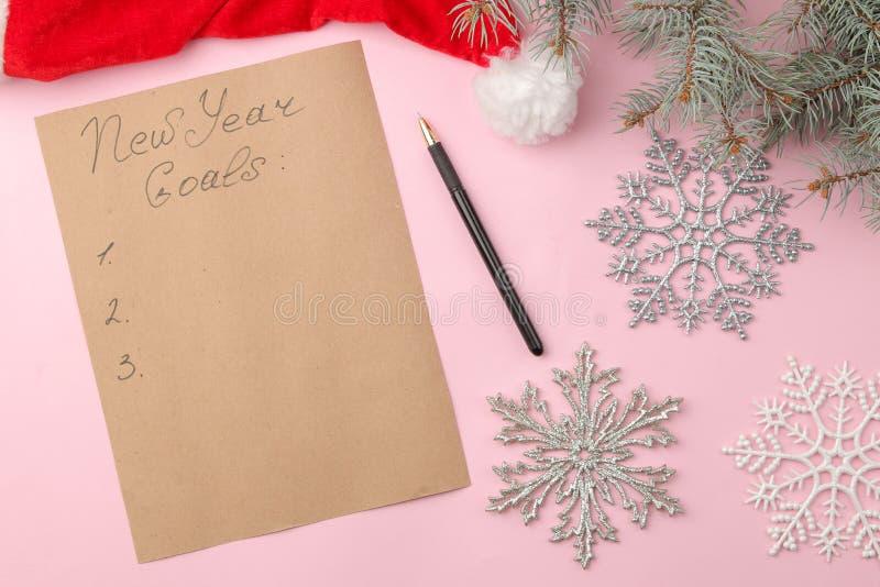 Nouvelles années de buts 2019 Texte sur un morceau de papier avec un décor de nouvelle année et un stylo sur un fond rose lumineu image libre de droits