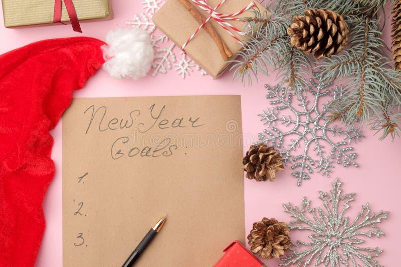 Nouvelles années de buts 2019 Texte sur un morceau de papier avec un décor de nouvelle année et un stylo sur un fond rose lumineu photos stock